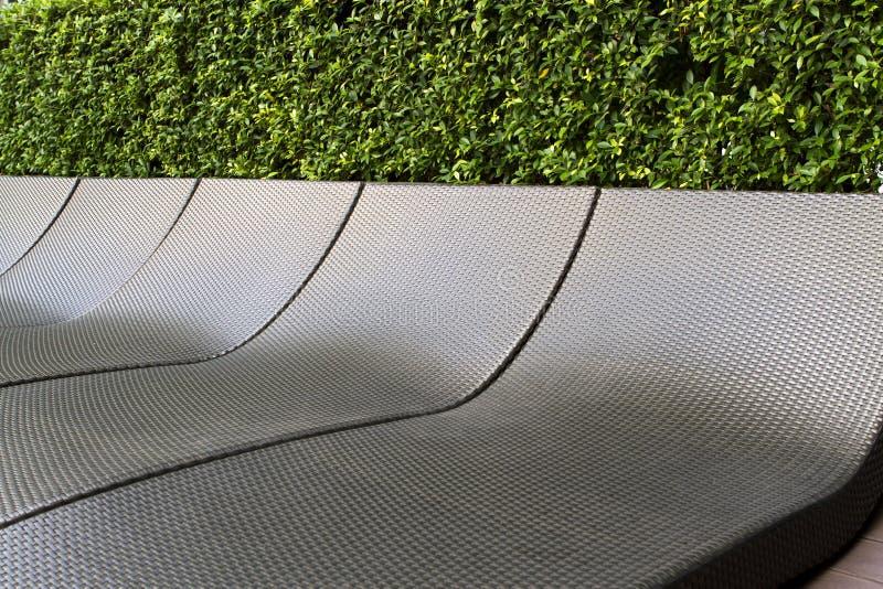 由塑料编织做的黑暗的sunbeds背景纹理  免版税库存图片