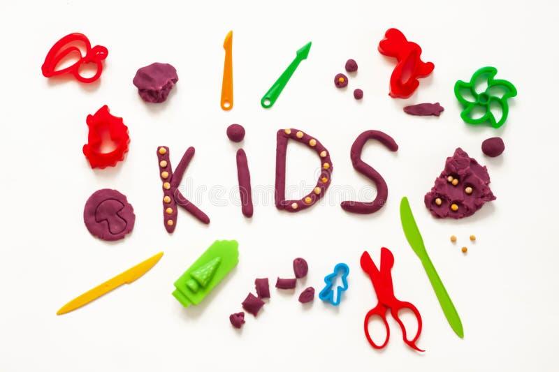 由塑造黏土和somemold工具做的文本孩子在白色背景 概念og儿童艺术 免版税库存图片