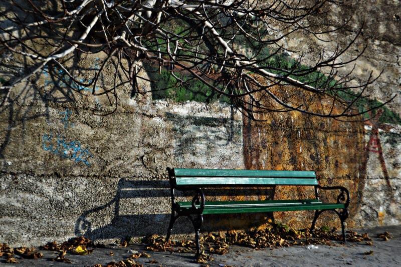 由墙壁丝毫墙壁街道画的绿色长凳作为背景 库存照片