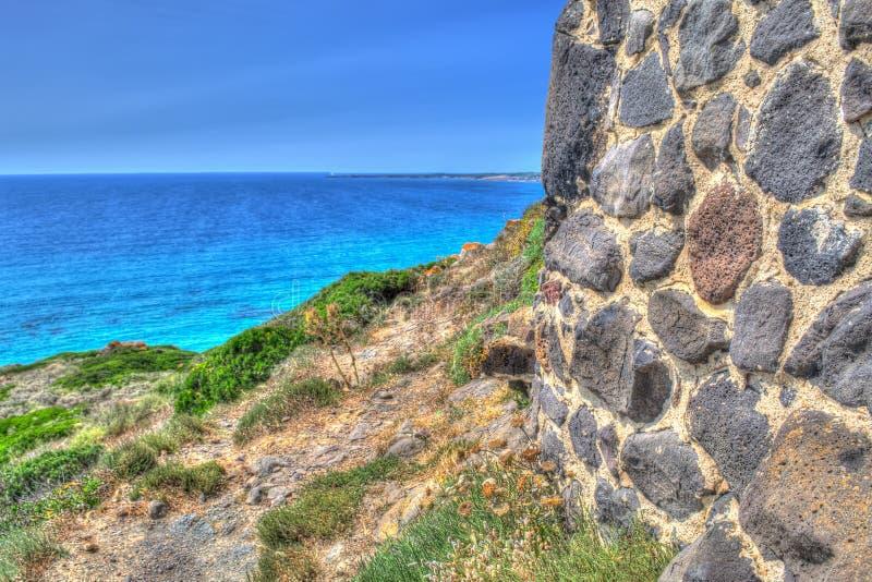 由岸的砖墙在撒丁岛 免版税库存图片