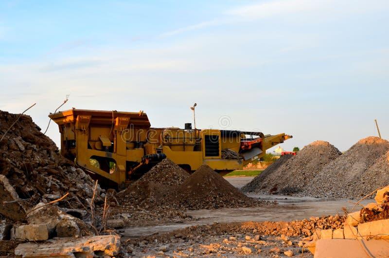 由工地工作或开采猎物的流动碎石机机器击碎的老混凝土板到石渣里 免版税库存照片
