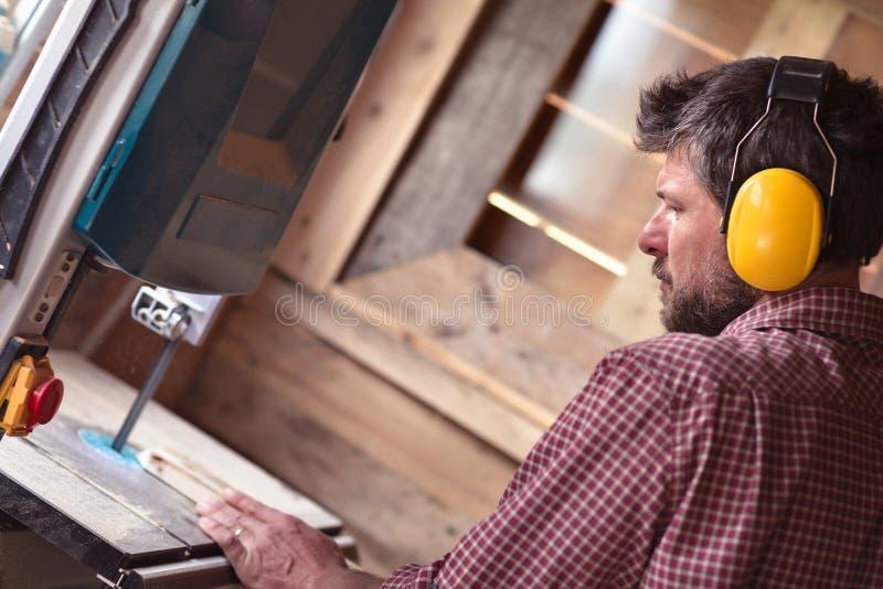 由带锯的男性木匠切口板条 库存图片