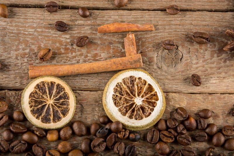 由干柠檬和肉桂条,由咖啡豆做的道路片断做的自行车反对概略的木板 库存照片