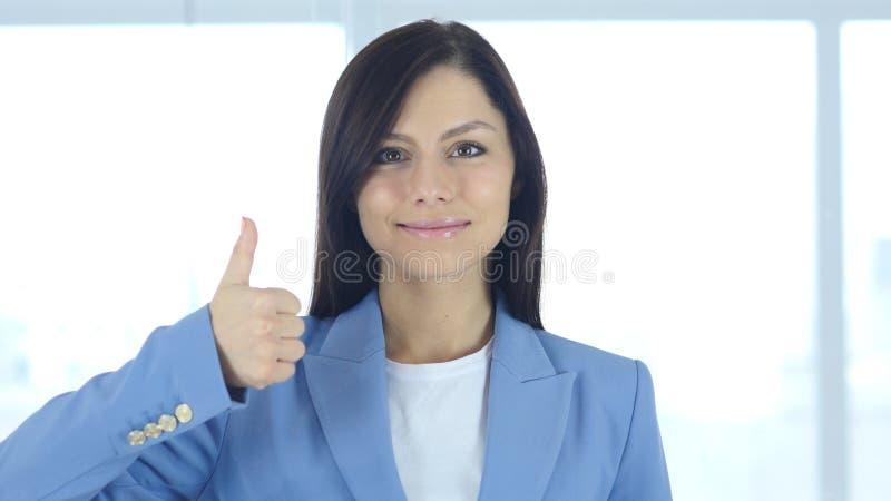 由年轻女实业家的赞许在办公室 免版税图库摄影