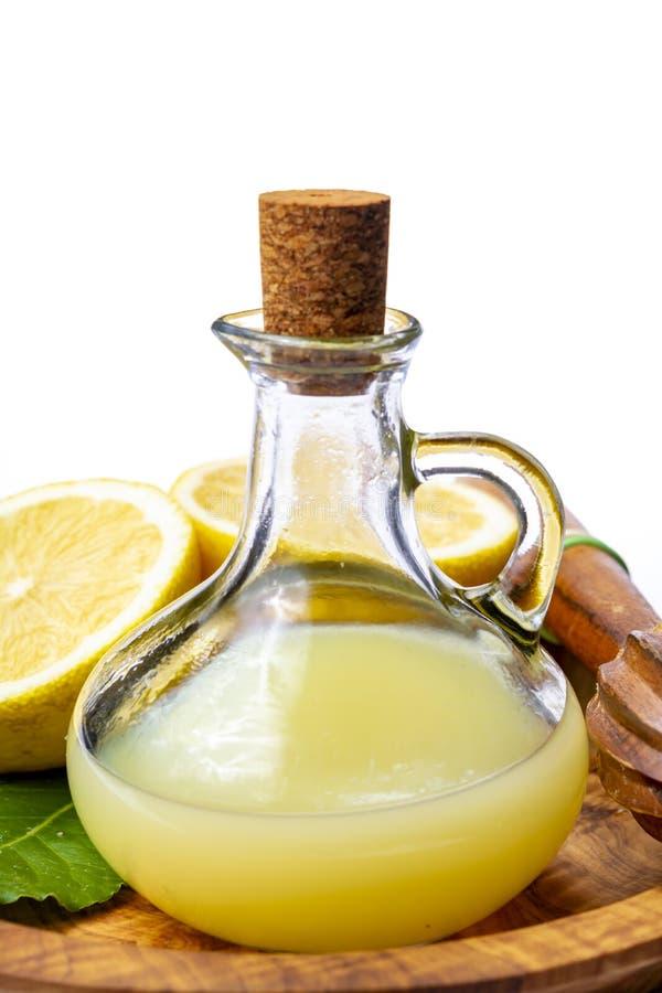 由成熟黄色西西里人的柠檬做的新鲜的柠檬汁用为烹调在玻璃瓶在橄榄色的木板材 库存图片