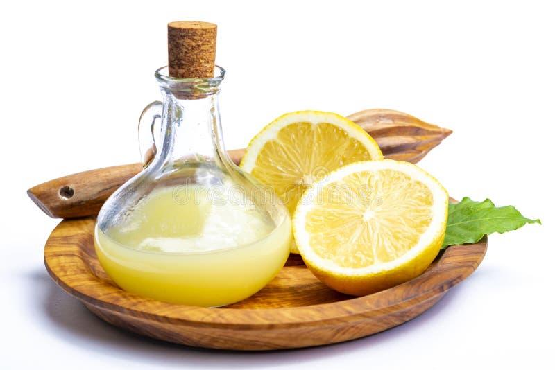 由成熟黄色西西里人的柠檬做的新鲜的柠檬汁用为烹调在玻璃瓶在橄榄色的木板材 库存照片