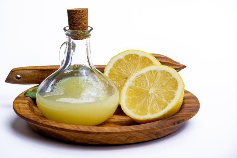 由成熟黄色西西里人的柠檬做的新鲜的柠檬汁用为烹调在玻璃瓶在橄榄色的木板材 免版税库存照片