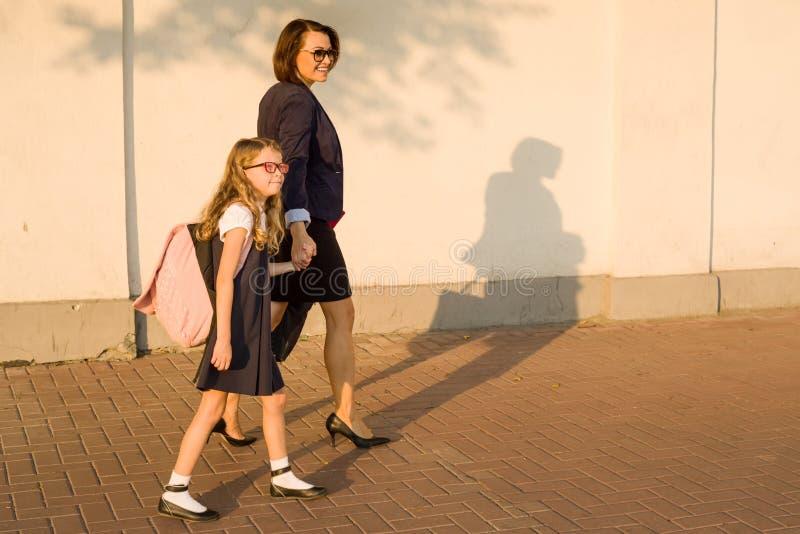 由手做父母抱孩子,上学 免版税图库摄影