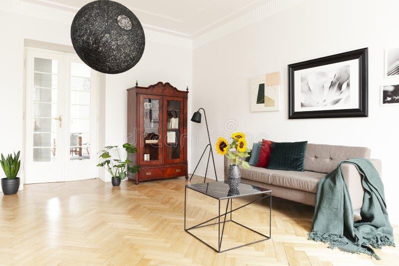 由折衷客厅内部的白色墙壁的黑暗,木,摆饰橱用黄色向日葵和艺术 免版税库存照片