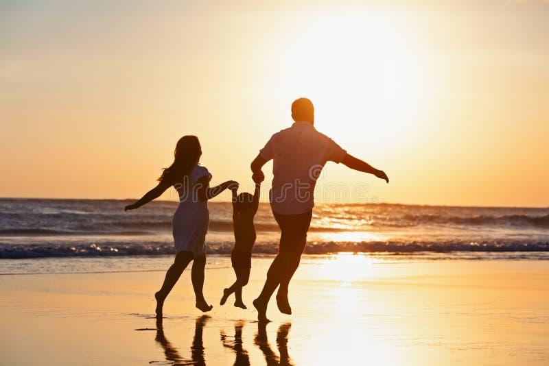 由日落海滩的幸福家庭赛跑 免版税库存照片