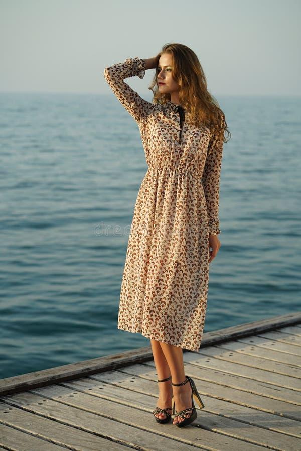 由日落的妇女在木码头 库存照片