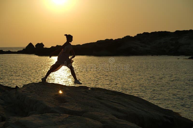 由日落的跳跃的妇女 免版税库存图片