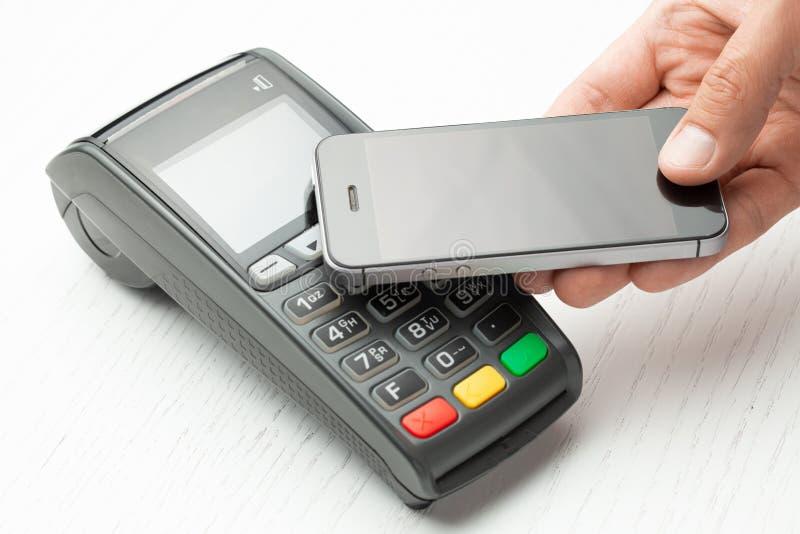 由智能手机电话的不接触的付款 POS终端NFC付款 概念的怎样选择购物的付款方法在商店 免版税库存照片