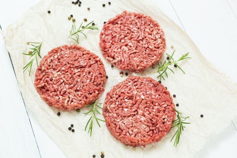 由有机肉做的三个未加工的汉堡包在白色木背景用香料 顶视图 库存图片