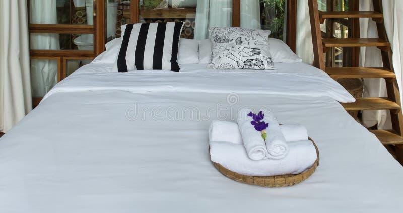 由木做的现代样式室为访客准备放松 与花的清洁毛巾在大床上的篮子 免版税库存照片