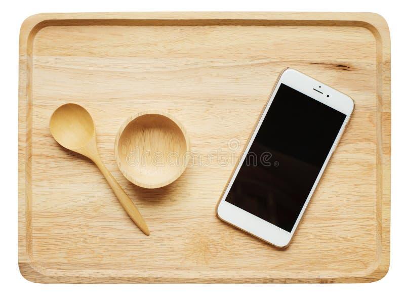 由木头做的聪明的电话和碗筷子在木板材 免版税库存图片
