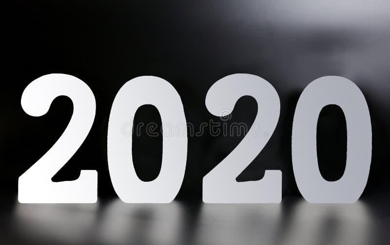由木白色数字2020做的年在黑背景 免版税库存图片