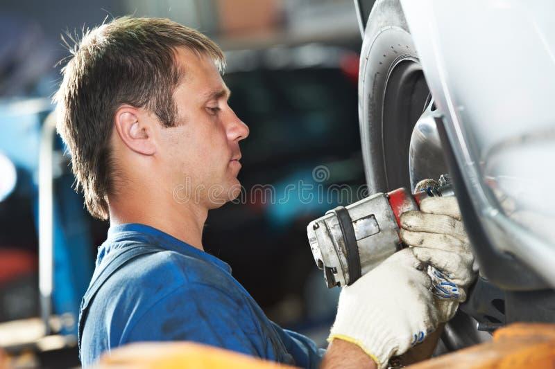 由板钳的汽车机械师拧紧的车轮 免版税库存照片