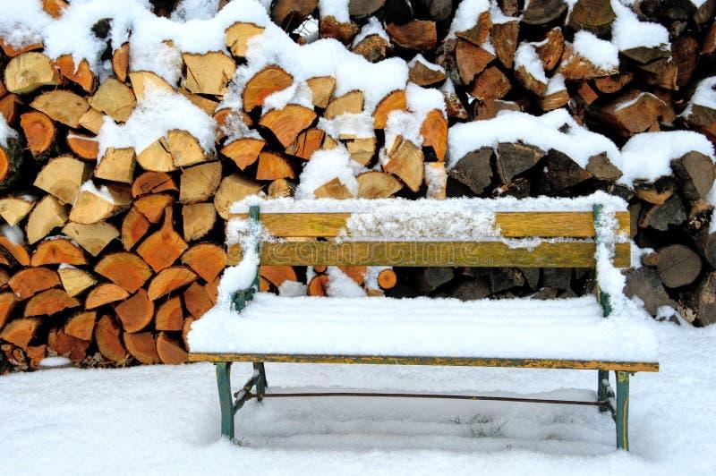 由柴堆的积雪的长凳 免版税库存图片