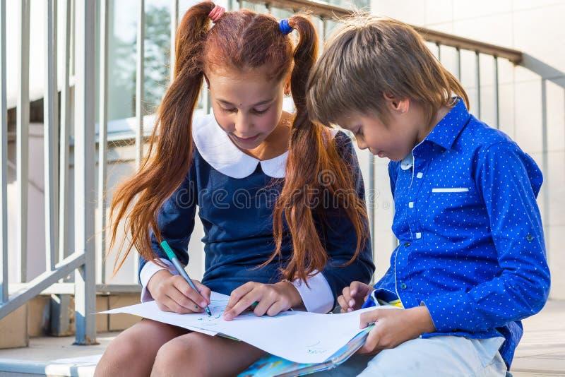 由标志的男孩和女孩油漆在学校附近 库存照片