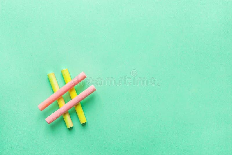 由横渡的五颜六色的桃红色黄色白垩蜡笔做的Hashtag标志在绿松石背景 Blogging社会媒介的网络 库存照片