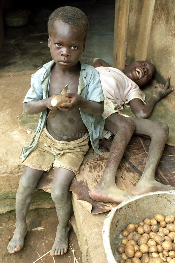 由残疾兄弟的乌干达男孩削皮土豆 免版税库存图片