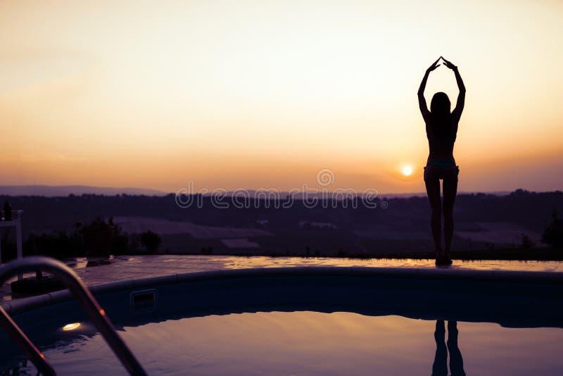 由水池的性感的妇女在日落期间 免版税图库摄影
