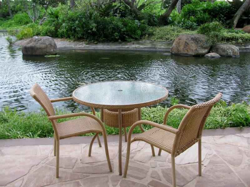 由池塘制表和在外部露台的两把椅子 库存图片