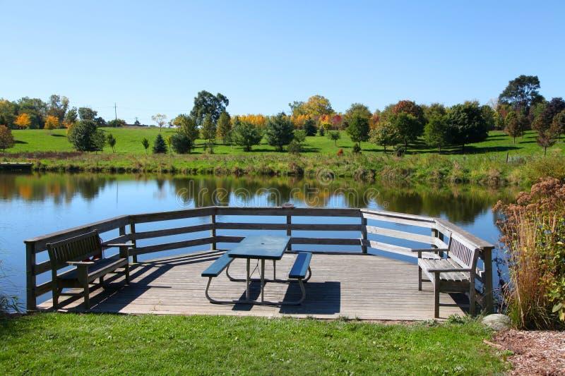 由池塘的野餐桌 免版税库存照片
