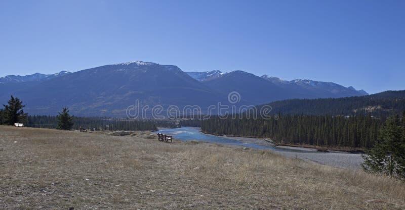 由河和山的长凳 免版税库存照片