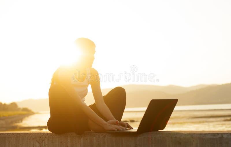由河的少妇与膝上型计算机的susnset的 免版税库存图片