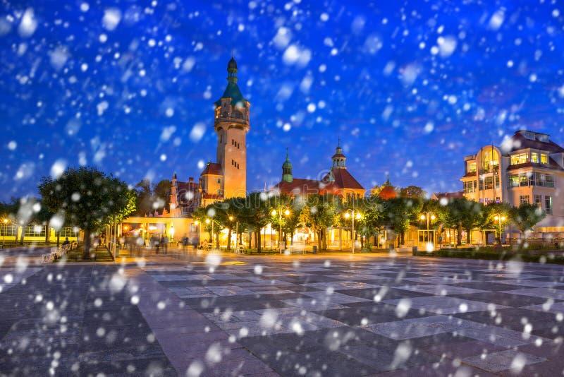 由波儿地克的码头的灯塔在索波特在落的雪的晚上 免版税库存图片
