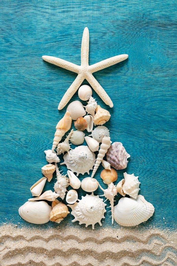 由海壳和海星做的圣诞树与沙子装饰 图库摄影