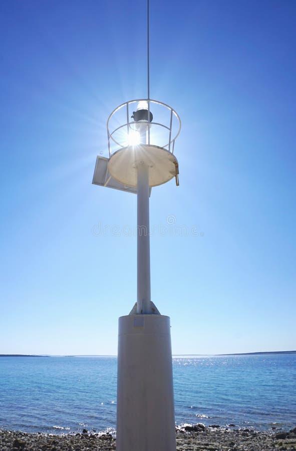 由海岸的光信号驻地剪影或灯塔与太阳光芒反射和天空蔚蓝和海在背景中 免版税库存照片