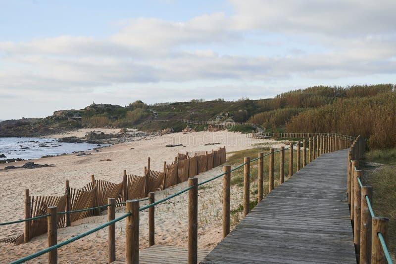 由海滩的木板走道在冬天下午 库存图片