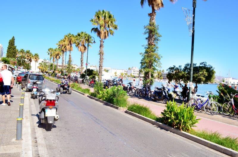 由海的典型的希腊街道有棕榈树和自行车道路的 Kos海岛,希腊 库存图片