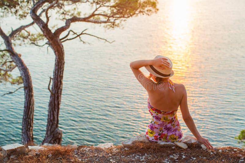 由海的坐的女孩日落和帽子的握手 免版税图库摄影
