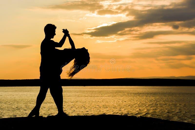 由海的夫妇跳舞辣调味汁日落的 免版税库存照片