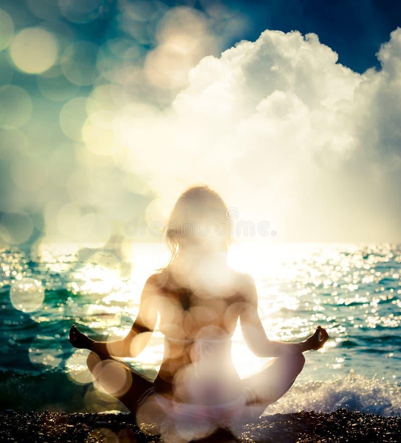 由海的女子实践的瑜伽 背景bokeh音乐注意主题 免版税图库摄影