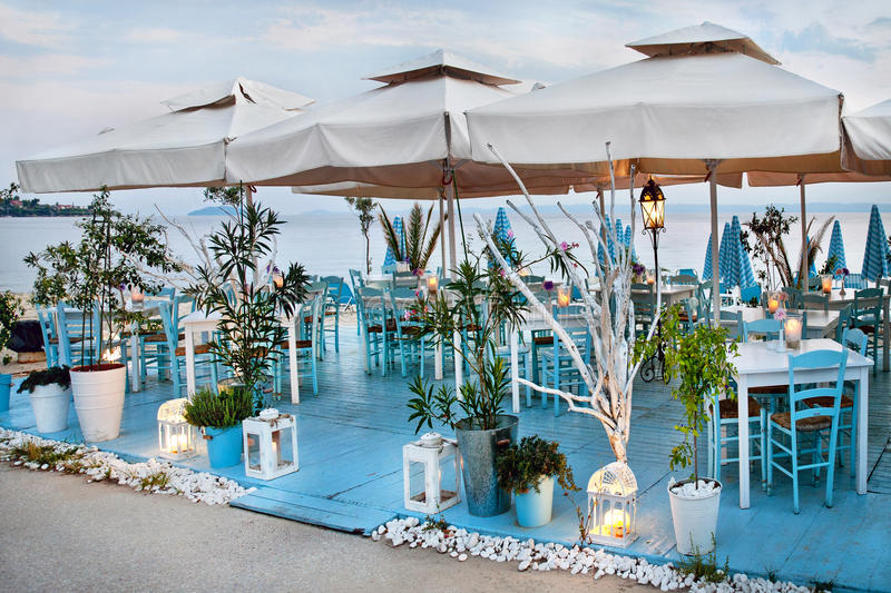 由海的希腊taverna有的蓝色传统木椅子和灯晚上, 26 Septembar 2016年 库存照片