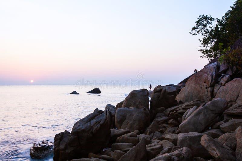 由海的平安的时间,站立和选址与照相机的男性游人,当享受在岩石海滩时的太阳设置 免版税库存照片