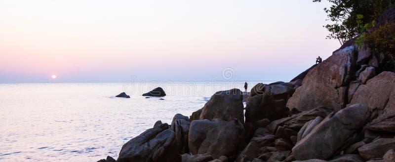 由海的平安的时间,站立和选址与照相机的男性游人,当享受在岩石海滩时的太阳设置 库存图片