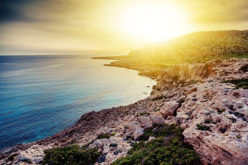 由海的惊人的明亮的美好的日落 蓝色的岩石和的天蓝色 免版税库存照片