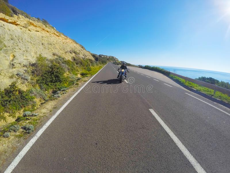 由海的摩托车乘驾在撒丁岛 库存图片