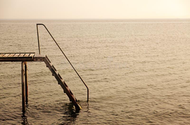 由海的日落在有一只台阶跳船的丹麦在前景 免版税库存图片