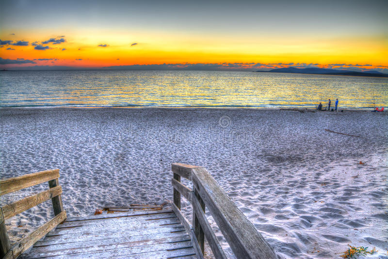 由海的木木板走道日落的 免版税库存照片