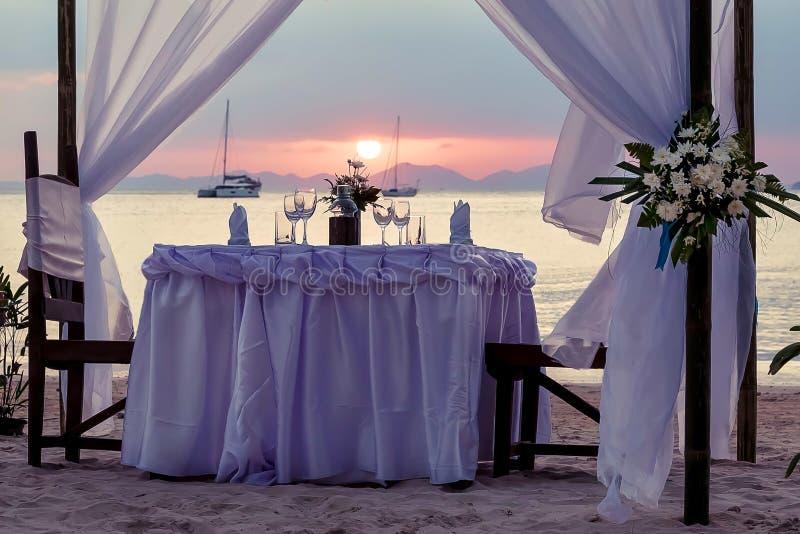由海的欢乐桌 装饰为一顿浪漫晚餐 反对日落、游艇和山背景  免版税库存照片