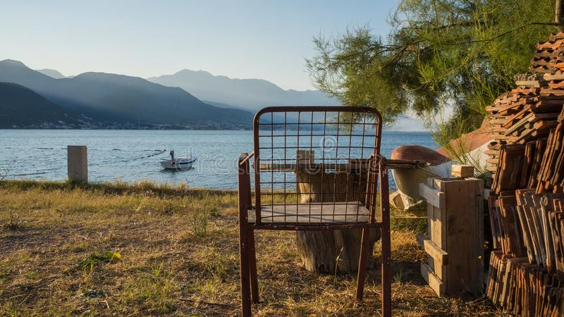由海的生锈的铁椅子 免版税库存图片