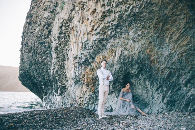 由海的美好的夫妇在岩石附近,新娘坐的女孩,新郎在她旁边站立,愉快 免版税库存照片