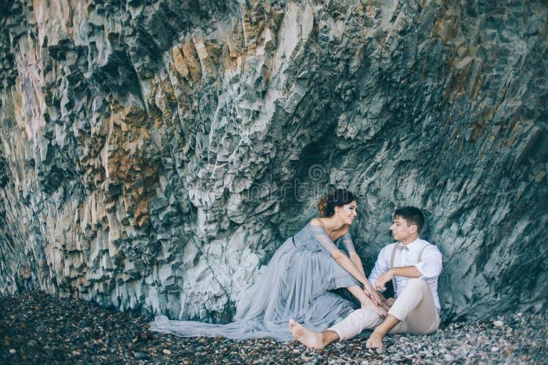 由海的美好的愉快的夫妇在岩石附近,赤足坐,微笑,谈话,笑,爱情小说 免版税图库摄影
